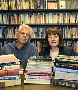 Barbara Pell and Bob Burkinshaw posing for a promotional shot, with stacks of books