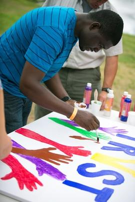 Orane Barrett painting a sign during the annual Community Day
