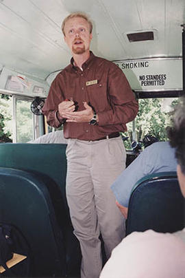 Staffer Rob Rhea standing inside a bus during O-Week