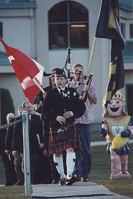 A piper leading a procession to the dedication ceremony for the new soccer field
