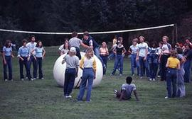 Students playing volleyball with a giant ball at the Fall Picnic.