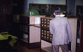 Individual approaching the card catalogue in the Vernon Strombeck Library.