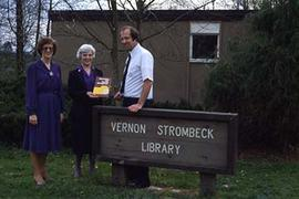 Library Director, David Twiest standing with two unidentified individuals beside the sign for the...