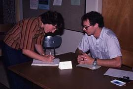 Unidentified faculty member assisting a student with registration during Orientation Week.