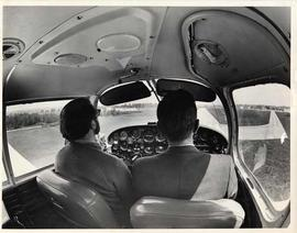 Two men in the front seats of a small plane at Langley Municipal Airport