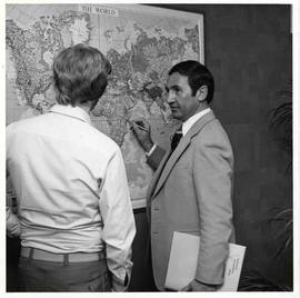 Marvin Kehler talking with a student and pointing on a map
