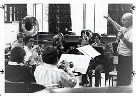 Faculty member leading a brass band during practice