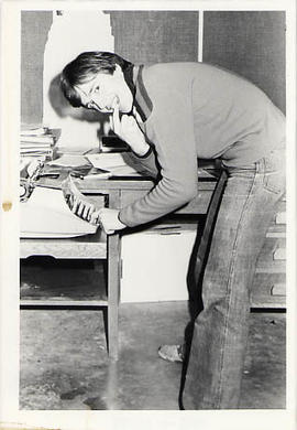 Student leaning over a typewriter