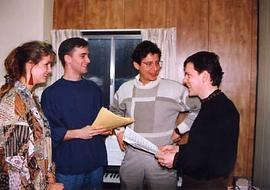 A mixed music ensemble talking in a room