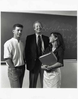 Promotional photograph of Craig Seaton with two students