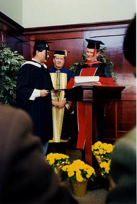 Donald Page presenting Adward Yang with his BBA