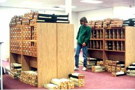 A student worker eyeing the piles of card catalogue drawers