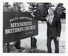 Staff member posing next to a church sign