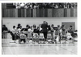Faculty member leading a brass band in the gym