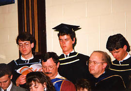 Choir members in prayer during the graduation ceremony