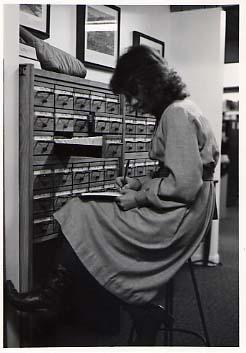 Student seated at a card catalogue in the Strombeck Library