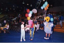 Child receiving a balloon from a student in costume