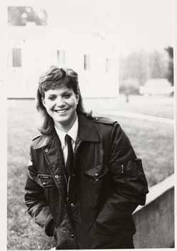 Female aviation atudent, in TWU uniform, walking on campus and smiling for the camera