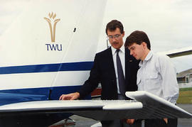 Matthew Edwards and Greg Brown examining the tail of a small aircraft