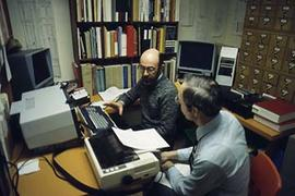 Unidentified individual speaking with a staff member at their computer work station in the former...