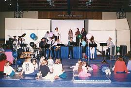 Music group performing for children in the gym