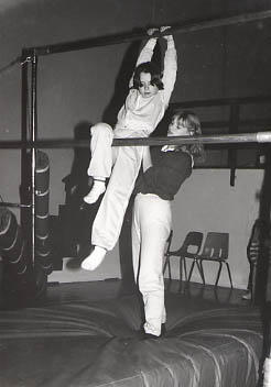 Student working with a girl on the uneven bars