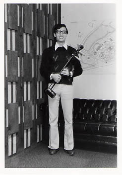Male student posing with a stringed instrument