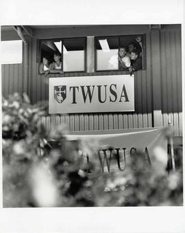 Five students at a window with a large sign reading TWUSA beneath it