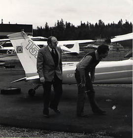 Instructor and student looking over an airplane