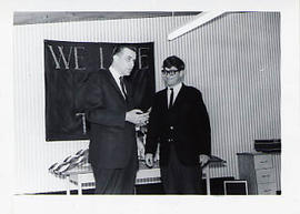Calvin Hanson handing a trophy to a student