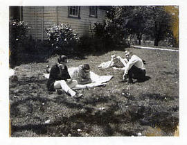 Four male students sitting on the lawn