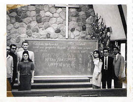 International students posing at the front of the chapel with a chalkboard
