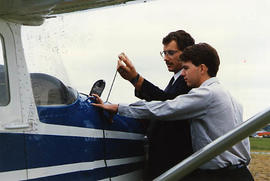 Aviation instructor checking the oil with a student
