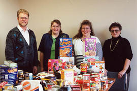 Staff posing with food collected for a Food Hamper Drive
