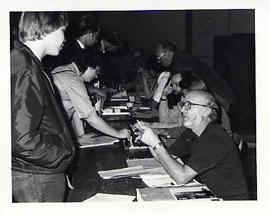 Faculty member helping a student register