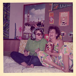 Two laughing female students on a bed in dorms