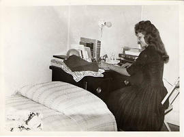 Student seated at a desk in her dorm room