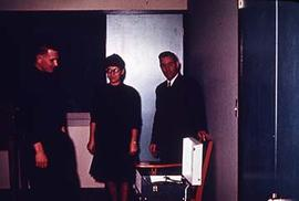 Unidentified individuals standing in a classroom.