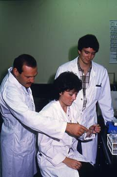 Unidentified faculty member assisting students with a science experiment.