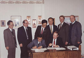 Dr Snider and a member of a Chinese delegation signing an affiliation agreement while others look on